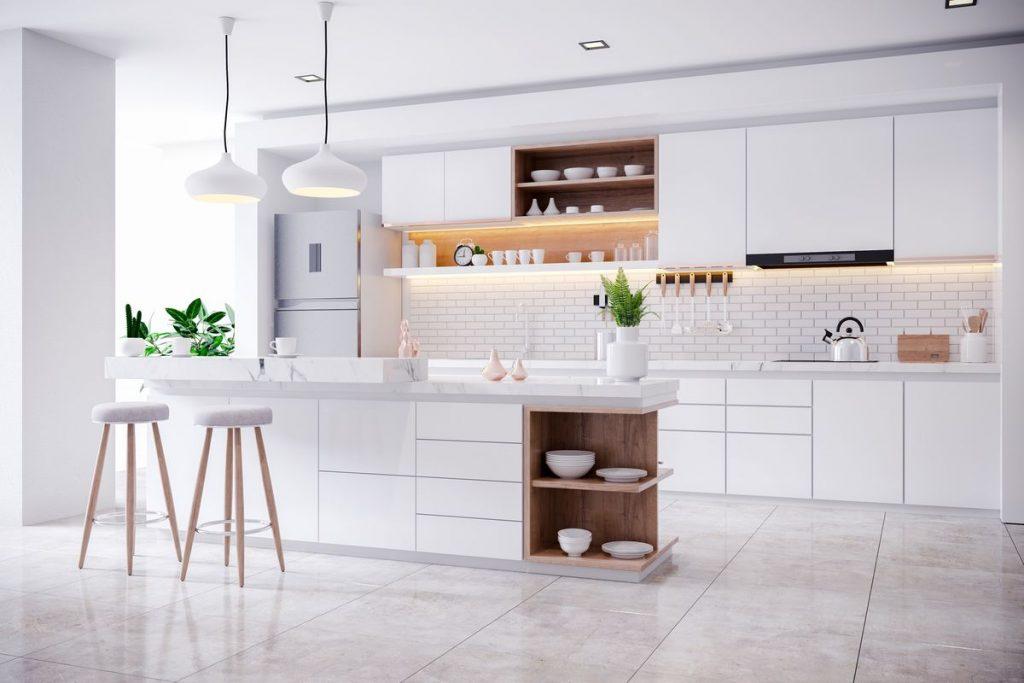Nowoczesna, jasna kuchnia z wyraźnie oświetlonymi półkami i blatem roboczym.